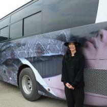 男性の紬姿で話題のバスと、仕掛け人の山口さん=28日、奄美市名瀬朝仁