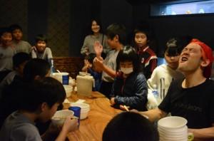 子どもたちと鶏飯の大食いにチャレンジする鈴木さん(右)=21日、奄美市名瀬