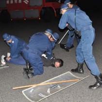 訓練でハイジャック犯を取り押さえる沖永良部署員=4日、和泊町の沖永良部空港