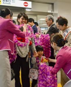 ピーチの乗客を歓迎する地元関係者ら=26日、奄美空港