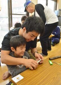 参加した児童に小刀の扱い方を教える満さん=22日、奄美市名瀬