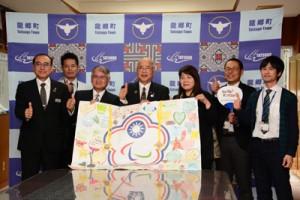 瀬留学童保育の子どもたちが作製した台湾パラ選手へのウエルカムボードを掲げる竹田泰典町長ら=20日、龍郷町