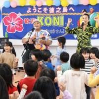 園児らのダンスに合わせウクレレを弾きながら熱唱するKONISHIKIさん=3日、伊仙町犬田布