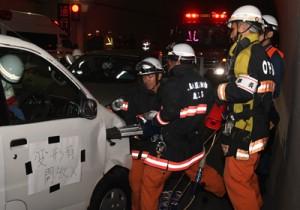 事故車両のドアを解体する消防署員=13日、瀬戸内町の網野子トンネル