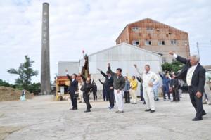 出発式で「頑張ろう三唱」をする与論島の糖業関係者ら=13日、同町
