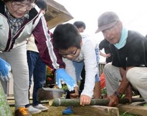 お年寄りから指導を受け、門松作りに挑戦する児童ら=26日、伊仙町面縄