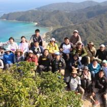 大山の山頂、ミヨチョン岳で記念撮影する受講生ら=15日、瀬戸内町請島(町企画課提供)