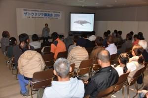 ザトウクジラの生態などを紹介した講演会=23日、奄美市名瀬