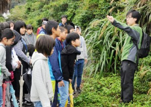 牧野さん(右)の外来種アメリカハマグルマ(下)の説明に聞き入る受講生ら=7日、瀬戸内町