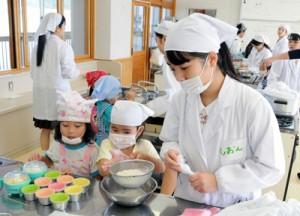 高校生から郷土菓子「ふくらかん」作りを学ぶ園児たち=16日、奄美市の県立奄美高校