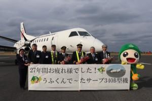 ラストフライトを前にサーブ機の前で記念撮影するJAC関係者=20日、喜界空港