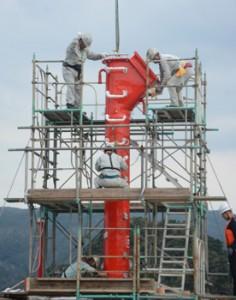 クレーンで慎重に基礎部へ降ろされる新灯台の灯塔=10日、名瀬港西防波堤