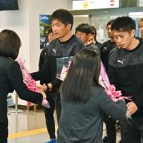 歓迎の花束を受け取る金監督(左)と薗田選手=20日、奄美市笠利町の奄美空港