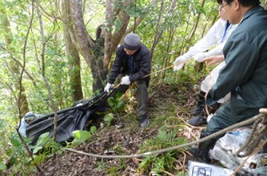ごみを詰めた袋を崖下から引き上げる参加者ら=23日、奄美市名瀬