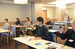身ぶり手ぶりを交えて、カタカナ接客英語に挑戦する参加者たち=14日、奄美市名瀬
