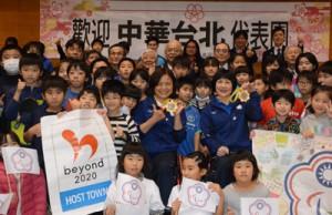 子どもたちから贈られたメダルを手に笑顔を見せる蕭さん(中央)と盧さんら=18日、龍郷町りゅうゆう館