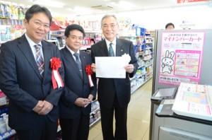 デモンストレーションで住民票の写しを発行した朝山市長(右)=6日、奄美市名瀬