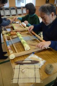 卓上機で、自らが収穫し乾燥させた芭蕉糸を織り、芭蕉布作りに挑戦する参加者=12日、宇検村湯湾