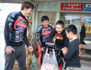 挑戦者に声援を送る(左から)前田さんと新納さん=19日、龍郷町中勝