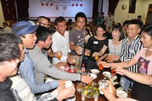 ベトナム式の乾杯で盛り上がる交流会の参加者=24日、和泊町のえらぶ長浜館