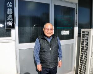 笑顔で会社の前に立つ佐藤徹義さん=2019年11月、神戸市長田区