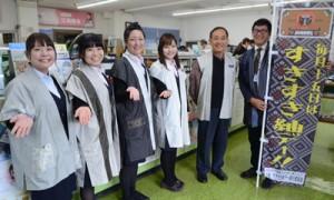 大島紬製の奄美ウエアを着た信組職員と南事務局長(右から2人目)=15日、奄美市名瀬