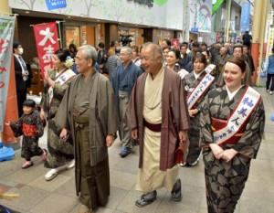 大島紬姿で商店街を練り歩き魅力をPRする参加者=5日、奄美市名瀬