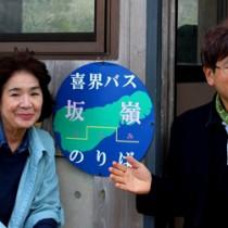 方言の集落名も記したバス停表示板をPRする(右から)喜界島言語文化保存協会の生島代表と緋月副代表(提供写真)