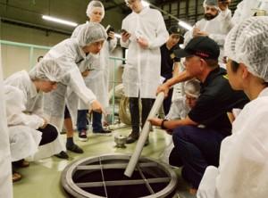 奄美黒糖焼酎の製造工程を視察する海外の専門家ら=24日、龍郷町の町田酒造