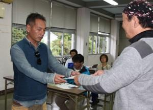 交付式で奄美群島認定エコツアーガイドの認定証を受け取る出席者=7日、奄美市名瀬