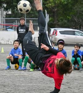 児童たちにオーバーヘッドキックの手本を見せる串山選手=11日、奄美市名瀬の朝日小学校校庭