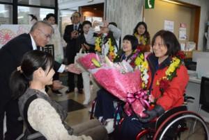歓迎の花束を受け取る(右から)蕭さんと盧さん=17日、龍郷町役場