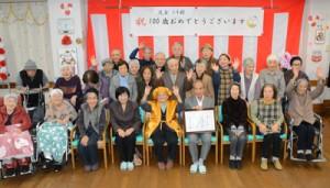 万歳で100歳の節目を喜ぶ児玉トキさん(前列中央)=15日、奄美市名瀬