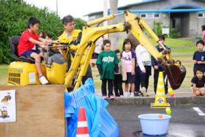 ショベルカーの試乗体験をする子ども=19日、喜界町早町の塩道長浜公園