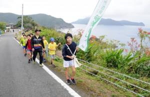 大島海峡の景色を楽しみながら歩く参加者=26日、瀬戸内町