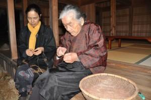 イトバショウの繊維をつないで糸を作る、与論民俗村の菊千代さん(右)と友子さん=12日、与論町