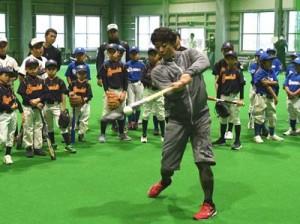 野球教室で打撃フォームを披露する鶴岡選手(中央)=12日、徳之島町徳和瀬
