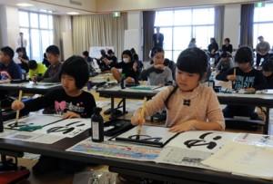 集中して課題を清書する参加者=7日、和泊町やすらぎ館