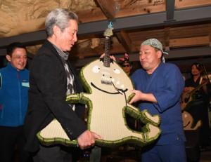 バンド主宰者の西脇さん(右)からばしゃ山村の奥社長に手渡されたケンムン型の畳ギター=22日、奄美市笠利町の「koya cafe」