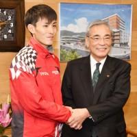 朝山市長と握手する服部選手(左)=17日、奄美市役所