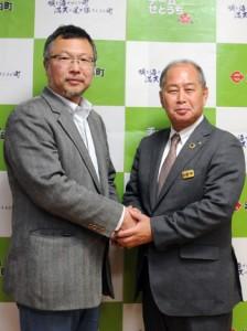 記者会見で、鎌田愛人瀬戸内町長(右)と握手する㈱TARGETの立石聡明社長=28日、同町役場