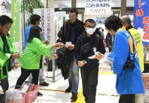 鹿児島からの乗客へ徳之島産タンカンを贈る農家や行政担当者=16日、天城町の徳之島空港