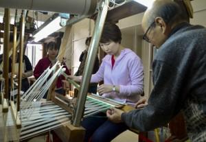 締め機の工程を体験するツアー参加者=23日、奄美市名瀬の市産業支援センター