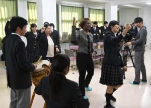 「ワイド節」を踊って高校生と交流するハギンス大使(右から2番目)=10日、天城町の樟南第二高校
