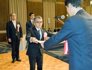 黒糖焼酎の入賞者を代表して表彰状を受け取る西平本家の小畠康幸代表取締役=14日、鹿児島市のホテル