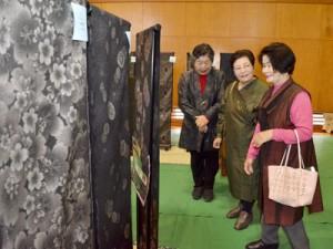 大島紬の展示に見入る来場者=16日、龍郷町