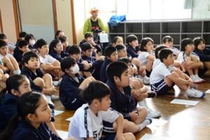 奄美に生息する希少動物などの映像に見入る児童=27日、奄美市名瀬の小宿小学校