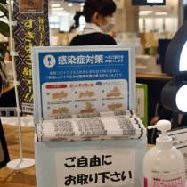感染症対策用に置かれたチラシと消毒用のアルコール液=27日、奄美市役所