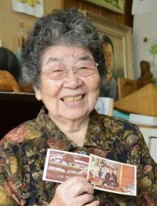 平田町にあったころのガジュマルと繁さんの写真を手にするキヌエさん=12日、名瀬浜里町の自宅