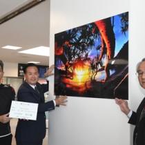 写真を寄贈した(左から)吉行さんと町田酒造の中村社長=27日、奄美市笠利町の奄美空港